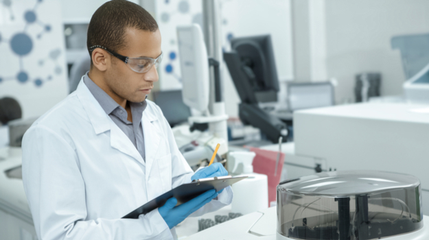 Researcher in laboratory taking notes on notepad