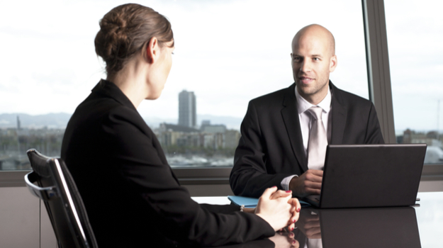 businesswoman in interview in corner office with exec looking at tablet