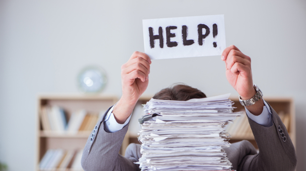 Businessperson hidden behind a stack of papers, holding up a sign stating 'help'