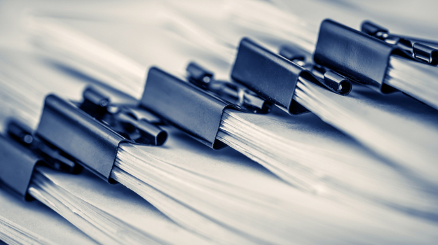 Stack of papers with clips bunching them together