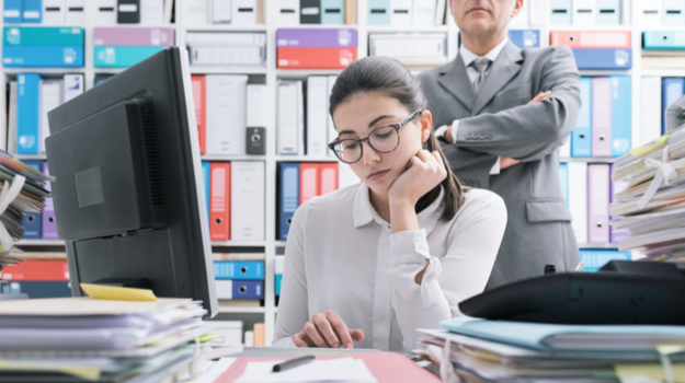 Man in suit stands over female employee's shoulder with his arms crossed, her desk is full of work