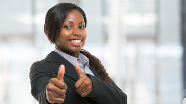 woman in suit smiling with both thumbs up