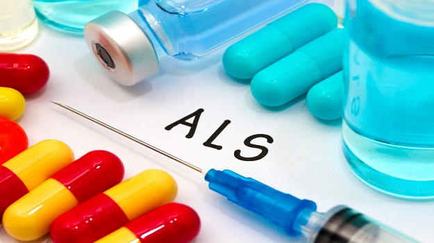 ALS words on a paper, next to red and yellow pills, a vial, and a syringe