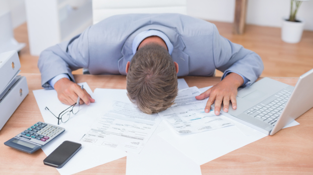 Man flopped over on desk on top of papers