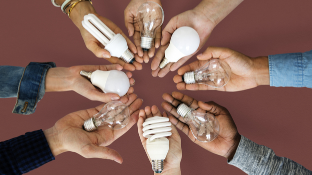 diverse hands in a circle each holding a lightbulb