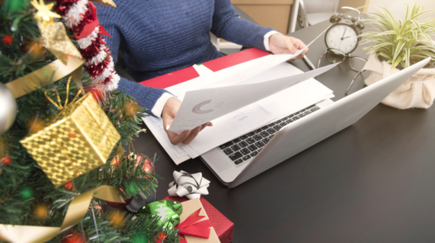 Worker sitting at desk next to christmas tree looking at papers and laptop