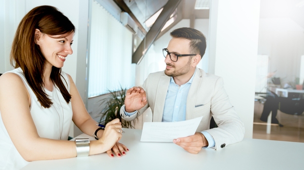 man and woman sitting at table at work and discussing performance
