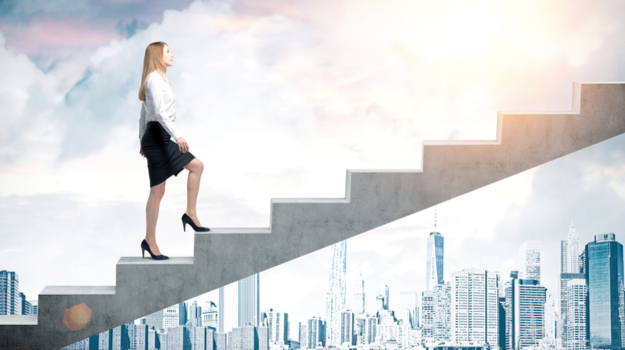 businesswoman climbing up stairs with skyline in background