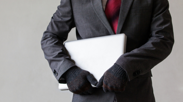man in suit and winter gloves holding closed laptop