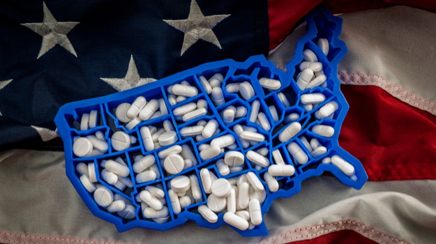 pill box in shape of US filled with white pills, placed on top of American flag