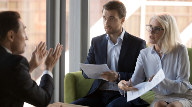 two colleagues pointing to paper angrily and talking to other coworker