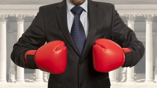 Man in suit with boxing gloves pointed towards each other