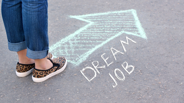 woman standing on pavement with words 'dream job' and an arrow in chalk