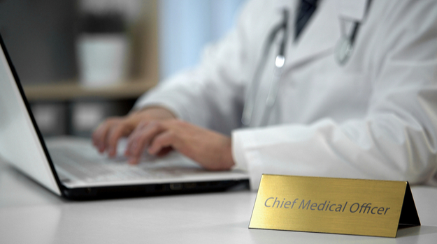 Doctor working on computer, with placard reading 'Chief Medical Officer'