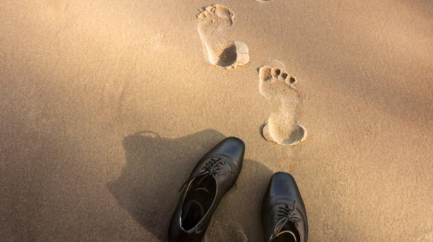 Empty Men's dress shoes on the beach, with footprints walking beyond the shoes