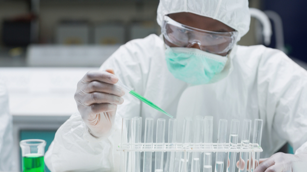 Chemist in protective suit filling test tubes with green liquid in the lab. Photo credit: Biospace.